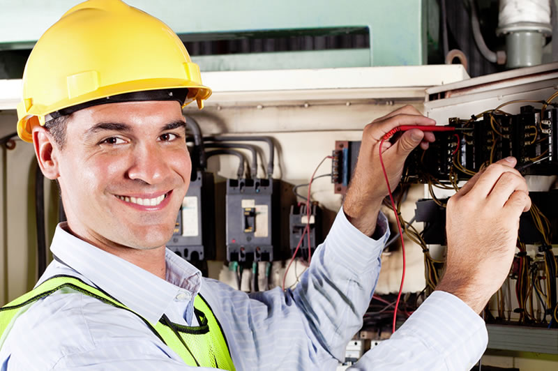 NJ electricians - smiling electrician testing circuits at panel